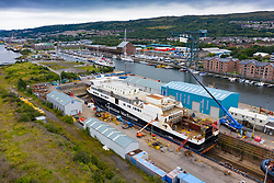Greenock, Scotland, UK. 16 August, 2020. Aerial view of controversial CalMac ferry MV Glen Sannox in Dales Dry Dock in Greenock on the River Clyde.The partially built ferry  which is well over budget and years late, was moved from Ferguson Marine shipyard in Port Glasgow to the nearby dry dock this week for modifications to the bow, repairs and cleaning.  Iain Masterton/Alamy Live News