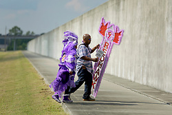 29 August 2015. Lower 9th Ward, New Orleans, Louisiana.<br /> Hurricane Katrina 10th anniversary memorial.<br /> Takiera Augustin (9 yrs) of the 9 Red Hawk Mardi Gras Indians and her father at the levee wall which gave way a decade earlier. <br /> Photo credit©; Charlie Varley/varleypix.com.