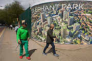 South Londoners walk past a regeneration project hoarding image at Elephant Park at Elephant & Castle, London borough of Southwark. Southwark Council's development partner, Lend Lease is regenerating over 28 acres across three sites at the heart of Elephant & Castle, in what is the last major regeneration opportunity in zone 1 London. The vision for the £1.5 billion regeneration is to build on the area's strengths and vibrant character in order to re-establish Elephant & Castle as one of London's most flourishing urban quarters. The Elephant & Castle regeneration is of a scale rarely seen in central London and includes almost 3,000 new homes, plus office, retail, community, leisure and restaurant space.