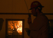 Flames from the Blue Cut wildfire is reflected at a window near Cajon Pass, north of San Bernardino, Calif., August 16, 2016. The fire is currently 9,000 plus acres, with 700 personnel on scene. Fifty-seven engines, 8 crews, 8 air tankers, 2 Very Large Air Tankers (VLATS), with additional firefighters and equipment on order. There is imminent threat to public safety, rail traffic and structures. With this being a very quickly growing wildfire, evacuation instructions have been issued. An estimated 34,500 homes and 82,640 people are being affected by the evacuation warnings.  AFP PHOTO / Ringo Chiu