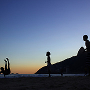 Locals play football during the late afternoon sunset on Ipanema beach, Rio de Janeiro,  Brazil. 6th July 2010. Photo Tim Clayton..The beaches of Rio de Janeiro, provide the ultimate playground for locals and tourists alike. Beach activity is in abundance as beach volley ball, football and a hybrid of the two, foot volley, are played day and night along the length and breadth of Rio's beaches. .Volleyball nets and football posts stretch along the cities coastline and are a hive of activity particularly at it's most famous beaches Copacabana and Ipanema. .The warm waters of the Atlantic Ocean provide the ideal conditions for a variety of water sports. Walkways along the edge of the beaches along with exercise stations and cycleways encourage sporting activity, even an outdoor gym is available at the Parque Do Arpoador overlooking the ocean. .On Sunday's the main roads along the beaches of Copacabana, Leblon and Ipanema are closed to traffic bringing out thousands of people of all ages to walk, run, jog, ride, skateboard and cycle more than 10 km of beachside roadway. .This sports mad city is about to become a worldwide sporting focus as they play host to the world's biggest sporting events with Brazil hosting the next Fifa World Cup in 2014 and Rio de Janeiro hosting the Olympic Games in 2016...