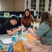 Erin celebrates the first night of Chanukah with her children at home. After dinner, lighting the Menorah and reciting a prayer, the kids opened cards from their aunt.