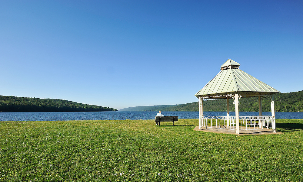 Finger Lakes, NY.  An hour or so past sunrise, the wind was buffeting the end of Hemlock Lake.  The chop on the water was intense, but not white caps, not yet.    The metal roof rattled on the little gazebo, and she didn't hear me as I came up the rise behind her. She was out there before me, staring off down the length of the lake, lost in thought I'm sure. I know the feeling, and I welcome the duty of the camera to stop the thinking and just do.  I took my time, relishing the green of a summer morning, and hating the cloudless sky.  She never turned.  I left her to her thoughts.