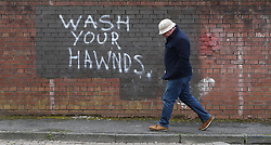A man walks past graffiti in the Belfast vernacular calling on people to wash their hands during the Covid-19 crisis in East Belfast.