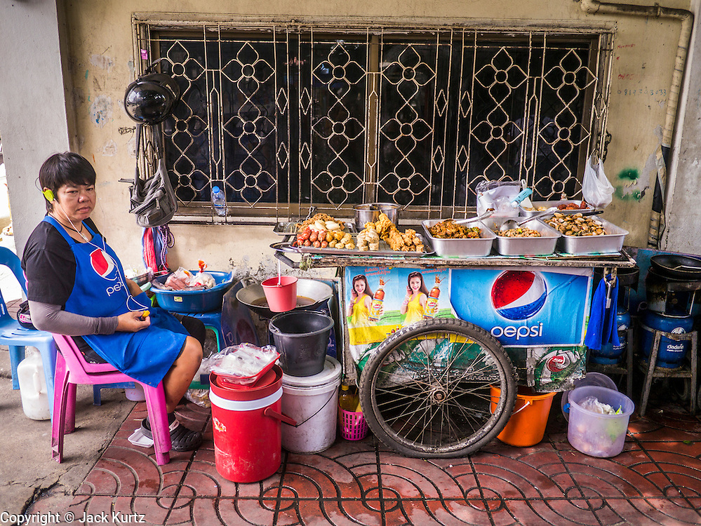 "05 OCTOBER 2012 - BANGKOK, THAILAND: A street vendor sits with her cart in the Chinatown section of Bangkok, Thailand. Thailand in general, and Bangkok in particular, has a vibrant tradition of street food and ""eating on the run."" In recent years, Bangkok's street food has become something of an international landmark and is being written about in glossy travel magazines and in the pages of the New York Times.       PHOTO BY JACK KURTZ"