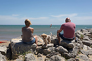 With their pet dog sitting between them, a couple sit on rocks watching windsurfers at the beach overlooking the Mediterranean Sea, on 23rd May, 2017, in Gruisson, Languedoc-Rousillon, south of France.