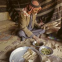 Dakhillala Suleiman (75), wearing a traditional keffiyeh head covering, eats Bedouin bread in wool nomad tent, Wadi Rum, Jordan.