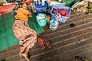 08 JUNE 2014 - YANGON, MYANMAR: A woman sleeps on a steamer sailing up the Yangon River. Yangon, Myanmar (Rangoon, Burma). Yangon, with a population of over five million, continues to be the country's largest city and the most important commercial center.      PHOTO BY JACK KURTZ
