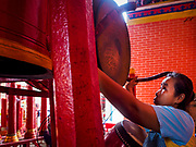 13 JULY 2017 - BANGKOK, THAILAND: A woman bangs a prayer bell at Chao Mae Thapthim Shrine in the Dusit district of Bangkok. The Chinese shrine is at the foot of Krung Thon Bridge and serves poor communities along the Chao Phraya River. The shrine is along a part of the riverfront the government wants to tear down to build an esplanade. The future of the shrine itself is unknown, but many of the communities around it could be evicted and razed.        PHOTO BY JACK KURTZ