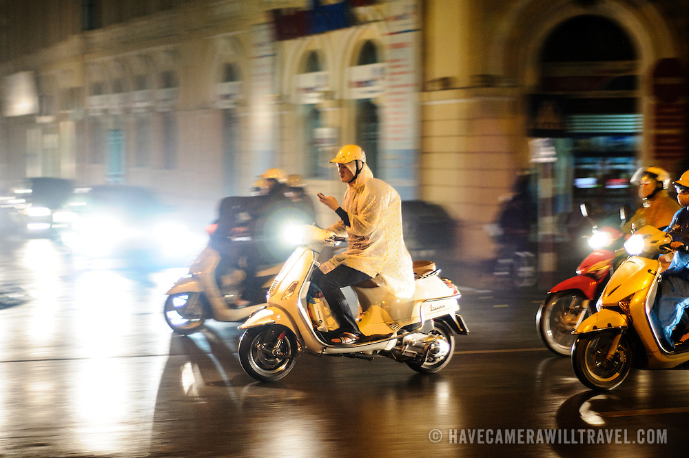 A man texts on his phone while riding a scooter through some of the hectic traffic of Hanoi's Old Quarter at night in the rain.