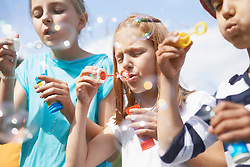 Girls blowing bubbles with bubble wands, Bavaria, Germany