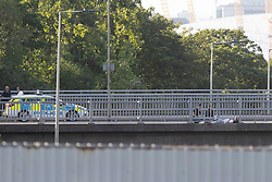 © Licensed to London News Pictures. 17/07/2020. London, UK. Police negotiators are speaking to a man (R) who is on the ledge of a bridge that passes over the A102.  Police have blocked the A102 and have cordoned off the bridge this has caused major traffic disruption in the area.  Photo credit: George Cracknell Wright/LNP