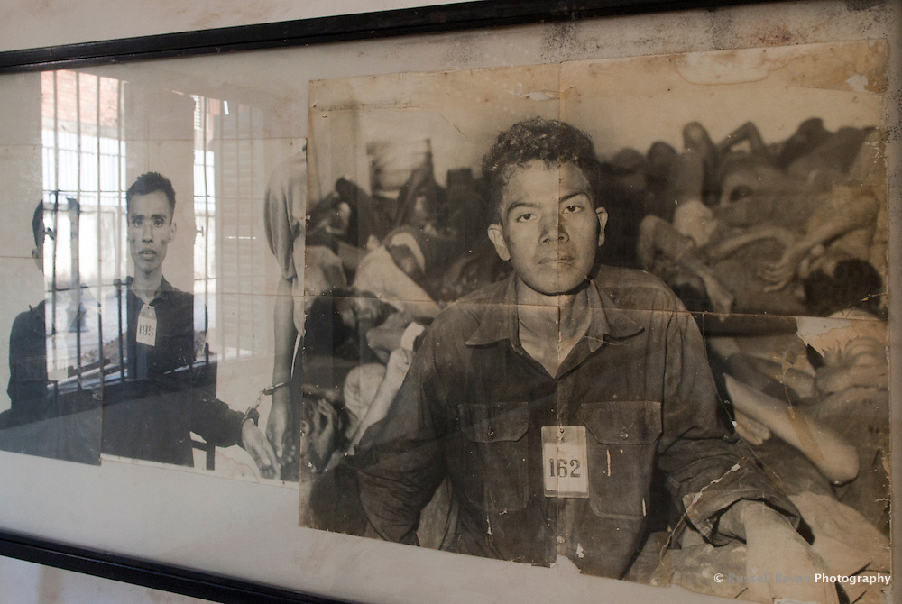 Image of a man standing in front of dead prisoners at Tuol Sleng Genocide Museum, Phnom Penh, Cambodia