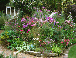 General view of garden at Ladywood with summer borders in full bloom. Wooden summerhouse
