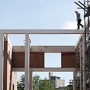 Nederland Rotterdam 28 mei 2008 20080528 Foto: David Rozing .Een bouwvakker op levensgevaarlijke manier/ bellend aan het werk op grote hoogte op nieuwbouwlokatie in de wijk Tussendijken in Rotterdam West. voorschriften inzake veiligheid en gezondheid arbeidsplaats arbeidsomstandigheden werken op hoogte ..Foto David Rozing