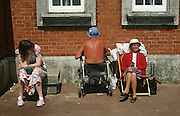 Ageing, elderly parents sunbathe with a teenage daughter as the father oddly faces a brick wall while sat in his wheelchair.