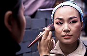 Zhang Lin, 23 leading Yue opera performer from the Xiao Bai Hua Shaoxing Opera Troupe having her make-up applied before a performance in a rural village close to Shaoxing City, Zhe Jiang province, China.                                She is one of the leading ights of Yue opera which as a form was born as late as the 1930's and she's been part of this troupe since she was 14. Today Yue opera like all traditional art forms faces stiff competition from television and all sorts of other entertainment and  as the troupe  no longer receive significant state funding, they must perform at least 150 times a year travelling far and wide across the country