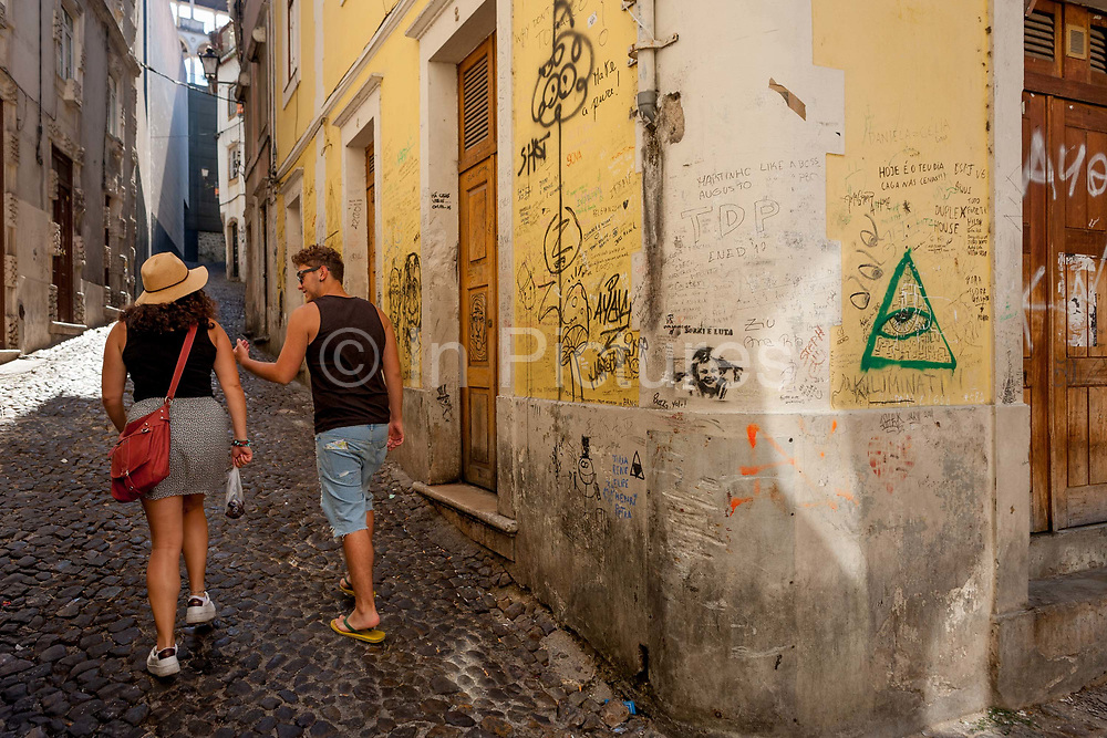 Students walk past scrawled messages on a street corner wal near Coimbra University, on 17th July, at Coimbra, Portugal.