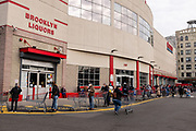 Brooklyn, NY - 7 April 2020. By 9:30 AM, the line to enter the grocery and warehouse store Costco on 3rd Avenue already stretches across the front of the building and West along the length of the South side back to 2d Avenue, North across the back of the store, East across the North side of the store, and continues to wrap again around the front to the entrance, seen about ¼ from the right of the photo. The store opens from 8 to 9 AM on Tuesdays through Thursdays for customers over 60, but some customers under 60 were seen waiting before 8.