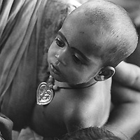 A child rests in his mother's arms in Mirpur Destitute Camp in Dhaka, Bangladesh, April 1977. Though she is impoverished his mother has spent precious pennies for bangles and make-up for her greatest source of pride - a son.  The dark circles around his eyes are believed to make them larger and more beautiful.