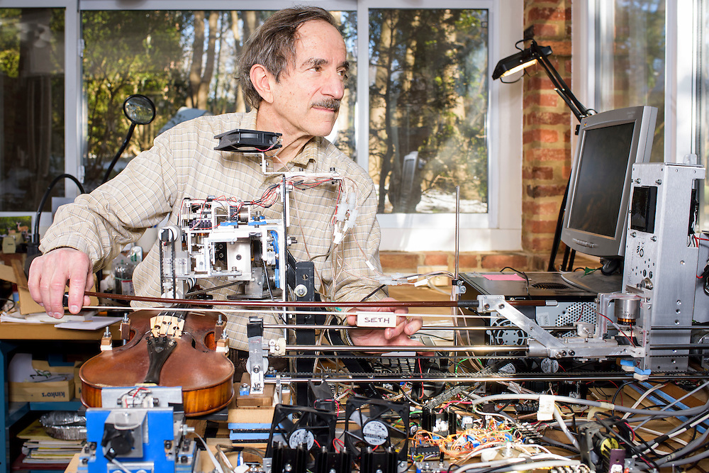 """Bethesda, Maryland - January 28, 2015: Instead of miniaturizing blood catheters, retired NIH mechanical engineer Seth Goldstein makes kinetic sculpture robots. """"Ro-Bow,"""" pictured, plays the violin. Seth applies resin to the bow. """"Why Knot"""" ties a neck tie. Goldstein credits his wife for the names. """"Cram Guy,"""" currently on display at the American Visionary Art Museum in Baltimore, is a crazy animated desk scene depicting a robot cramming for a test only to nod off to sleep. <br /> <br /> CREDIT: Matt Roth for The New York Times<br /> Assignment ID: 30169995A"""