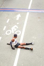 ING New York CIty Marathon: Meb Keflezighi sits on ground after finishing race