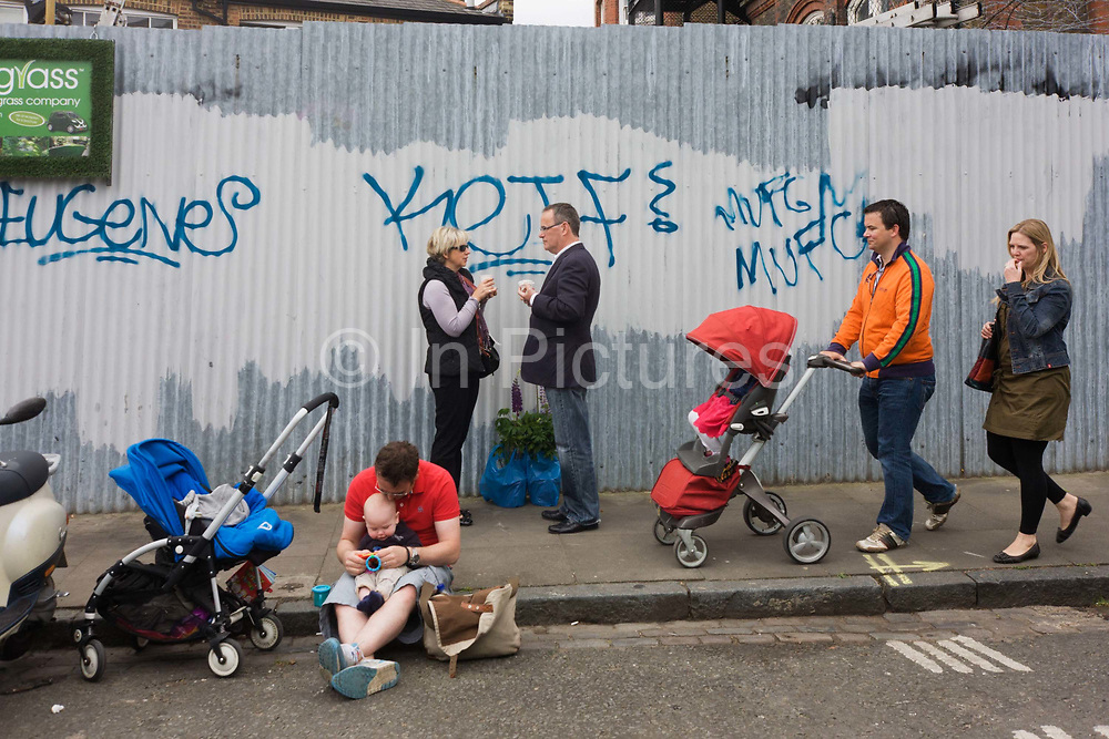A dad entertains his young child while another couple walks past with their buggy. Another husband and wife stand with plants, drinking coffee in a side street off Columbia Road flower market. Graffiti has been sprayed on the corrugated sheeting including tag names and the mark of Manchester United Football club (MUFC). The older couple stand with recent purchase of plants for their home and the younger dad with the pushchair wears a bright orange track-suit style top.