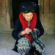 An elderly Yao woman wearing her traditional clothing sew outside her home in Ban Nammy, Luang Namtha province, Lao PDR.  One of the most ethnically diverse countries in Southeast Asia, Laos has 49 officially recognised ethnic groups although there are many more self-identified and sub groups. These groups are distinguished by their own customs, beliefs and rituals. Details down to the embroidery on a shirt, the colour of the trim and the type of skirt all help signify the wearer's ethnic and clan affiliations.