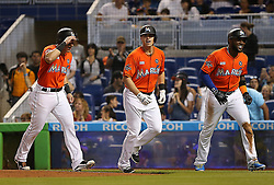 June 4, 2017 - Miami, FL, USA - Miami Marlins' Tyler Moore, center, is greeted at homeplate by teammate Derek Dietrich, left, and Marcell Ozuna, right, after his second inning, three-run home run against the Arizona Diamondbacks on Sunday, June 4, 2017 at Marlins Park in Miami, Fla. (Credit Image: © Patrick Farrell/TNS via ZUMA Wire)