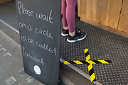 As the number of UK Coronavirus cases rose to over 8,000, it was announced that thousands of 15-minute home tests could be made available within days to those self-isolating with symptoms, A pair of feet stand at the counter of Monmouth Coffee where hazard tape is crossed on the ground to socially distance customers. Because of trading restrictions, the retailer is only selling other drinks at their Borough shop, on 25th March 2020, in London, England.