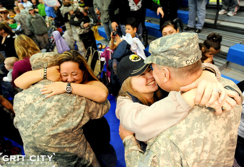 Spouses Lt. Col. William Cook, and Col. Penelope Cook, right, and Spc. Gregory Mingledorff and Lauren Mingledorff embrace at a Joint.Base Lewis-McChord homecoming ceremony at Wilson Gym March 3, 2010. The soldiers, with I Corps, completed a 12-month deployment to Iraq, where they served as the headquarters element for Multi-National.Corps Iraq, supporting U.S. and multi-national units deployed in support of Operation Iraqi Freedom..