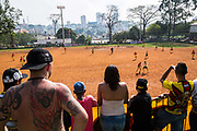 "Sao Paulo amateur ""Várzea"" Championship between Colorado and Santa Cruz teams in Villa Formosa district, Sao Paulo city. Fans sing and dance to a Samba beat to support their team. `The amateur ""Várzea""championship was born before the professional  game took hold throughout Brazil and its roots lie in the city of Sao Paulo, the creator of such a championship, which is fiercely contested by all teams that participate in the competition. Before each game begins the participating team fan base drum up support with a colourful diplay of fireworks and a passionate drum beat of Samba."