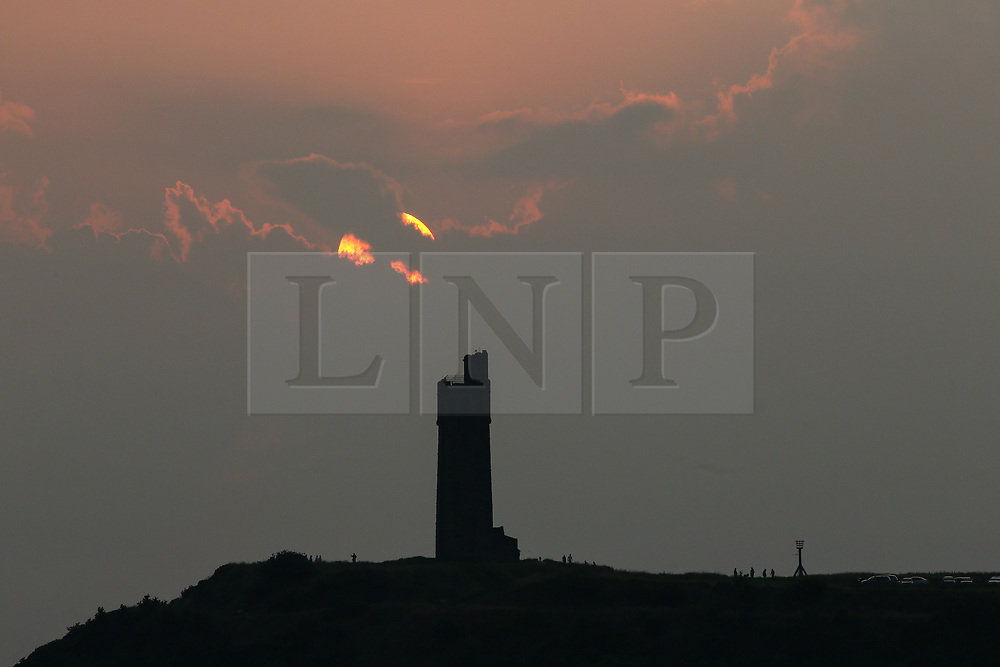 © Licensed to London News Pictures. 21/07/2021. Huddersfield, UK. The Sun sets behind Castle Hill in Huddersfield, West Yorkshire on Wednesday evening after another day of high temperatures. Photo credit: Adam Vaughan/LNP