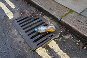 A water bottle that has been filled by human urine, has been discarded in the gutter on a residential street in south London, on 27th january 2021, in London, England. Delivery courier drivers often complain about the lack of toilet facilities on their driving routes and so feel the need to drop their filled bottles in the street. Local residents however, find this disgusting behaviour anti-social.