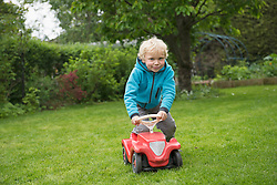 Small blonde boy playing with toy car in garden