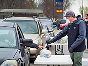 """11 APRIL 2020 - DES MOINES, IOWA: JORDON ELWELL, owner and CEO of Midwest Foods, uses a plastic table to pass a ready to cook pasta meal to a motorist during a food distribution in Des Moines. Most non-essential businesses in Iowa are closed until 30 April. Because of business closings causes by the Novel Coronavirus (SARS-CoV-2) pandemic, well over 100,000 Iowans filed first time claims for unemployment in the last three weeks, more than applied during the peak of the Great Recession of 2008. Local food banks have seen an unprecedented spike in people seeking nutritional assistance. Midwest Foods, a Des Moines based company and owner of Ginos Fine Italian Foods, gave away 1,000 complete dinners with sauce, noodles, salad, and dressing Saturday morning. People started lining up 3 hours before the food distribution began. The food distribution was done following """"social distancing"""" guidelines and all of the workers wore masks and gloves.     PHOTO BY JACK KURTZ"""