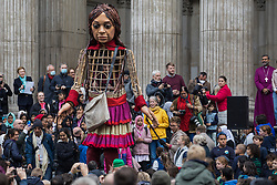 Little Amal, a giant puppet of a Syrian refugee girl fleeing conflict, leaves St Paul's Cathedral after being welcomed by the dean Dr David Ison and a crowd including many children on 23rd October 2021 in London, United Kingdom. The 3.5-metre puppet, which is nearing the end of an 8,000km journey from the Turkish-Syrian border to Manchester in support of refugees, climbed the steps of St Paul's Cathedral to present a wood carving of a ship at sea from St Paul's birthplace at Tarsus in Turkey to the dean.
