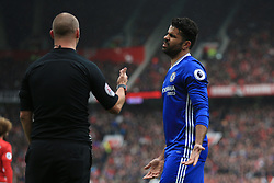 Referee Robert Madley (left) lectures Chelsea's Diego Costa