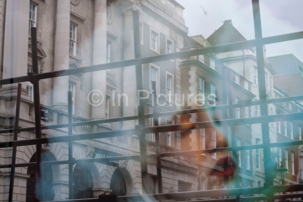 Reflection of a photograph of a models face and hair in scaffolding on 5th March 2021 in London, England, United Kingdom.