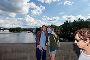 """A couple is doing a """"selfie"""" with a smart phone on Charles Bridge. The Charles Bridge (Czech: Karlův most) is a famous historic bridge that crosses the Vltava river in Prague, Czech Republic and is probably the Nr.1 tourists magnet in the city."""