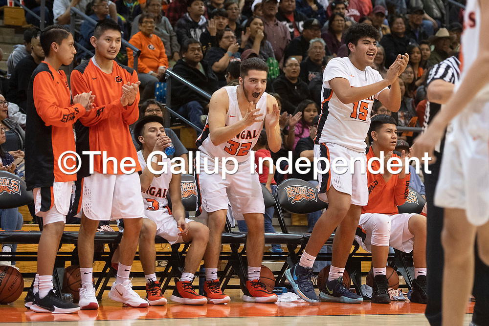 The Gallup Bengals bench cheer on their teammates during Friday night's district 1-4A tournament championship game against Kirtland Central Broncos at Gallup High School in Gallup. The Bengals beat the Broncos 60-41.
