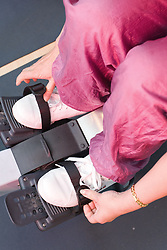 Woman strapping her feet into the rowing machine at her sports leisure centre,