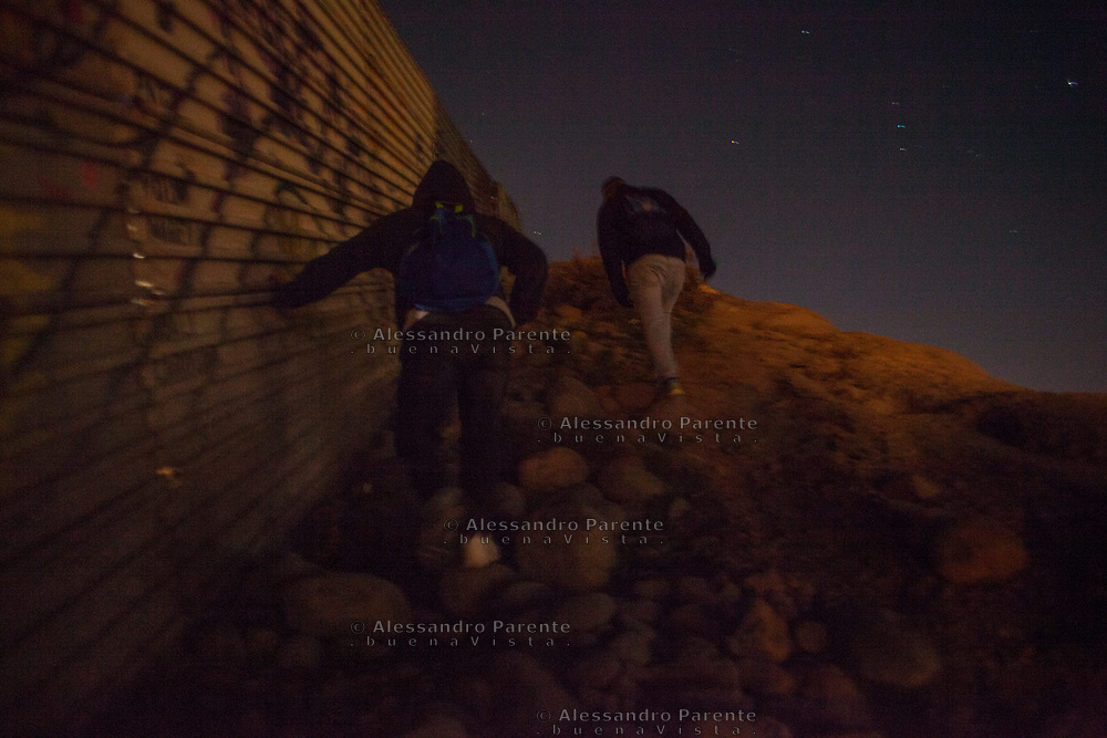 Two migrants walking through the border to find a place where to climb.