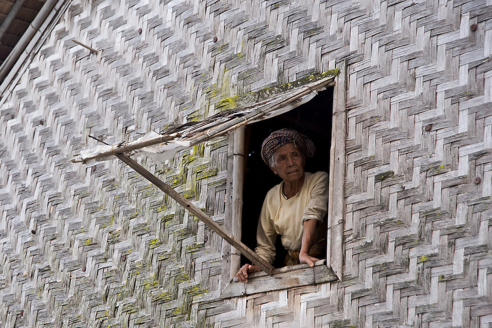 A woman peers from the window of her house on the Inle Lake, Myanmar.