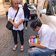 A street vendor in Rome makes bracelets for passersby near the Trevi Fountain.