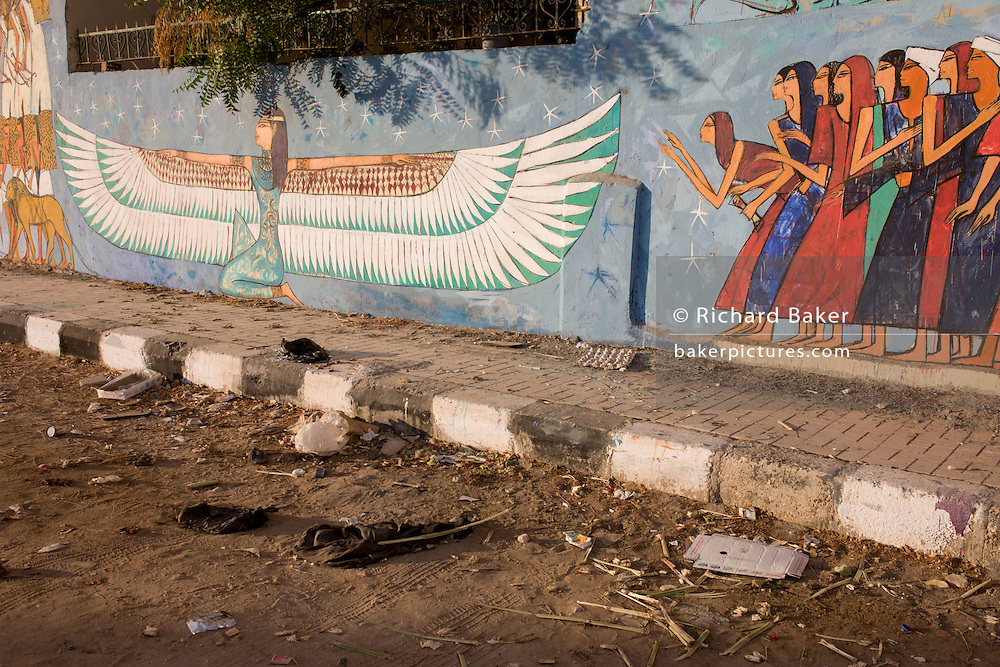 Modern hieroglyphic artwork painted on a wall of local wasteground in the village of Gezirat on the West Bank of Luxor, Nile Valley, Egypt.