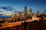Traffic flows through downtown Seattle as the city buildings begin to light up during the evening twilight.