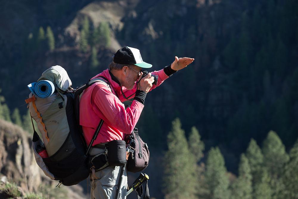 Photographer using his hand to shade his camera's lens, Wenaha River Canyon, Oregon