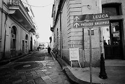 Reportage sviluppato ad Alessano (LE). Viene presa in considerazione fotograficamente, la gente che popola il paese nei suoi bar, piazze, strade, giardini pubblici. Ed, insieme a questa, i particolari caratterizzanti il luogo...Persone passeggiano per le vie del centro storico.