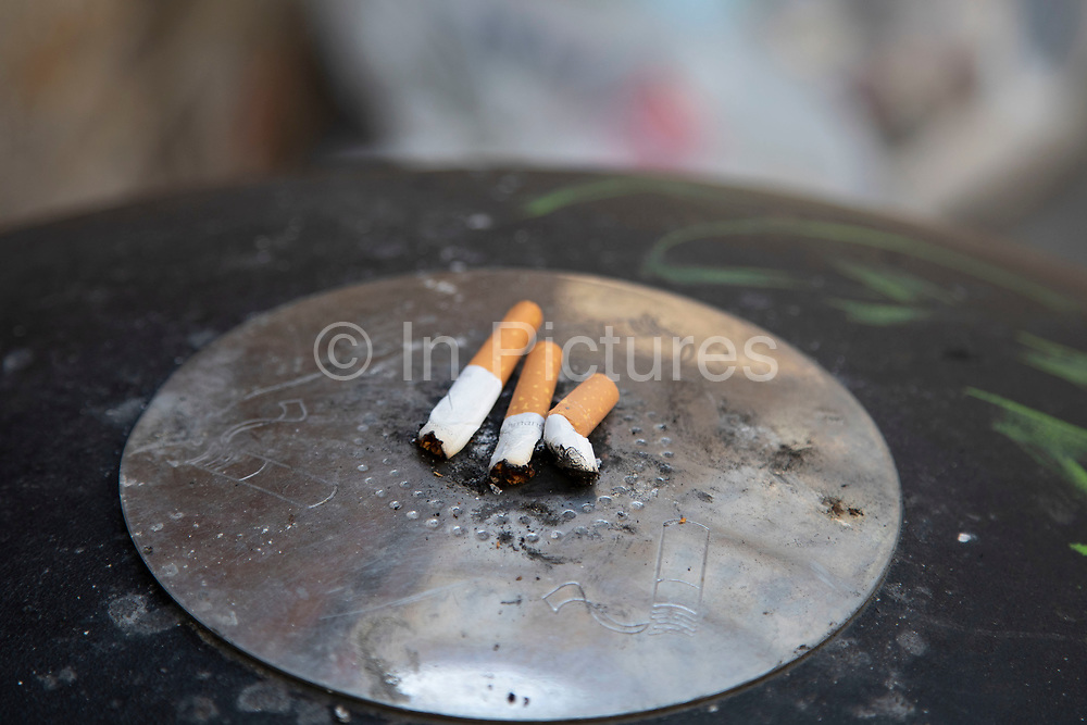 Cigarette butts on top of a bin which acts as an ashtray in London, England, United Kingdom. Smoking is in decline in the UK due to health concerns.